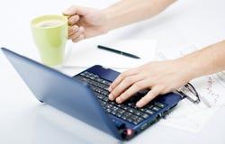 Bemannen Sie das Arbeiten an Laptop mit Kaffee und Tagesordnung Stockbild