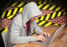 Bemannen Sie das Arbeiten an Laptop am Schreibtisch gegen Vorsicht aufgenommene Wand im Hintergrund Lizenzfreies Stockbild