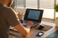 Bemannen Sie das Arbeiten mit Notizbuch im Büro, Geschäftsarbeitsplatz Stockfoto