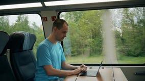 Bemannen Sie das Arbeiten an seinem modernen Laptop beim Reisen mit dem Zug lizenzfreie stockbilder