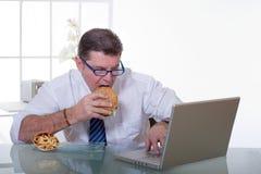 Bemannen Sie das Arbeiten und essen Sie unhealt Nahrung lizenzfreies stockbild