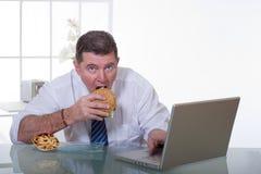 Bemannen Sie das Arbeiten und essen Sie unhealt Nahrung stockbilder
