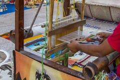 Bemannen Sie das Arbeiten am Webstuhl, spinnt traditionellen nationalen Teppich mit Kamelen Fokus auf dem Gewebe stockfotografie