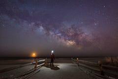 Bemannen Sie das Aufpassen des Mondes und der Milchstraße-Galaxie zu steigen lizenzfreie stockfotografie