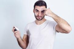 Bemannen Sie das Auftragen der Gesichtscreme auf Stirn und Backen, Mannschönheit stockfoto