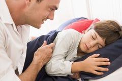 Bemannen Sie das Aufwecken des jungen Jungen beim Bettlächeln Lizenzfreie Stockfotografie