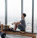 Bemannen Sie das Ausarbeiten auf Reihenmaschine im Eignungsstudio an der scyscraper Luxushotelturnhalle lizenzfreies stockfoto