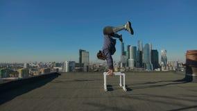 Bemannen Sie das Ausdehnen auf das Dach gegen den Hintergrund der Stadt stock footage