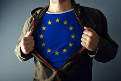 Bemannen Sie das Ausdehnen der Jacke, um Hemd mit Flagge der Europäischen Gemeinschaft aufzudecken Lizenzfreie Stockbilder