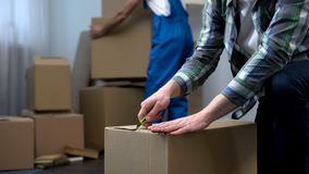 Bemannen Sie das Auspacken von Sachen in der neuen Wohnung, die Umzugsunternehmenarbeitskraft, die Kästen holt lizenzfreie stockfotos
