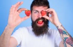 Bemannen Sie das bärtige Blinzeln mit der roten Beere, defocused Perfektes Erdbeerkonzept Betrachten Sie meine Beere Hübscher Hip Lizenzfreie Stockbilder