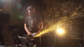 Bemannen Sie das Bearbeiten des Winkelschleifers in der Werkstatt Schmied, der mit Metall arbeitet ein Mann in der Funktionskleid stock footage