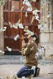 Bemannen Sie das Beten und Geld fallend vom Himmel Stockbild