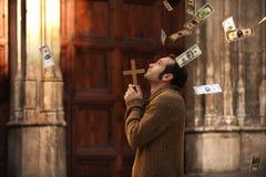 Bemannen Sie das Beten und Geld fallend vom Himmel Lizenzfreie Stockfotografie