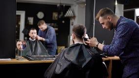 Bemannen Sie das Betrachten der Reflexion, die im Friseursalon während der Meister sitzt, der Haar herstellt stock video footage