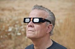 Bemannen Sie das Betrachten der Sonnenfinsternis mit Eklipsegläsern Stockfotos