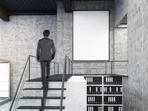 Bemannen Sie das Betrachten der Wand im Büro mit Treppe und Plakat Stockfotos