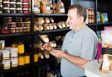 Bemannen Sie das Betrachten der Zusammenstellung der Lebensmittelgeschäftprodukte in den Regalen lizenzfreie stockbilder