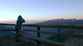Bemannen Sie das Betrachten des Bergblicks bei Sonnenaufgang vom hölzernen Balkon und das Trinken des Heißgetränks vom Becher, ho stock video footage