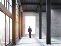 Bemannen Sie das Betrachten des großen Plakats im ehemaligen Fabrikgebäude Stockfoto