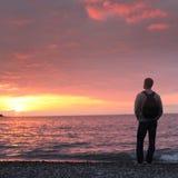 Bemannen Sie das Betrachten des Sonnenuntergangs auf einem Strand Lizenzfreies Stockbild