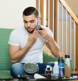 Bemannen Sie das Betrachten des Spiegels und das Rasieren des Bartes mit Trimmer Stockfotos