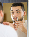 Bemannen Sie das Betrachten des Spiegels und das Rasieren des Gesichtes mit Rasiermesser Lizenzfreie Stockfotografie