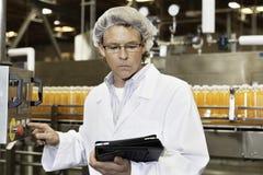 Bemannen Sie das Betrachten des Tablet-PCs beim Arbeiten in abfüllender Fabrik lizenzfreie stockfotografie