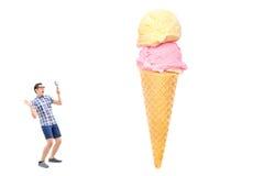Bemannen Sie das Betrachten einer Eiscreme durch ein Vergrößerungsglas Stockfotografie