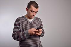 Bemannen Sie das Betrachten seines intelligenten Telefons während Versenden von SMS-Nachrichten Lizenzfreies Stockbild