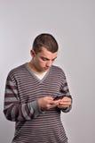 Bemannen Sie das Betrachten seines intelligenten Telefons während Versenden von SMS-Nachrichten Stockfotos