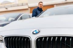 Bemannen Sie das Betrachten von BMW-Auto, bevor Sie Entscheidung treffen, um sie zu kaufen Stockfotografie
