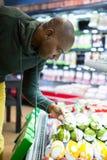 Bemannen Sie das Betrachten von Waren im Lebensmittelgeschäftabschnitt beim Einkauf lizenzfreies stockbild
