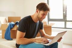 Bemannen Sie das Bewegen in neues Haus unter Verwendung der Laptop-Computers Lizenzfreies Stockfoto