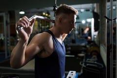 Bemannen Sie das Biegen von Muskeln auf Kabelmaschine in der Turnhalle Lizenzfreie Stockfotografie