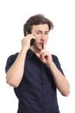 Bemannen Sie das Bitten um Ruhe mit dem Finger auf Lippen, während um das Telefon ersucht Stockfotos