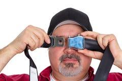 Bemannen Sie das Blicken durch ein Loch in einer Sicherheitsgurtschnalle Lizenzfreies Stockfoto