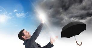 Bemannen Sie das Blockieren der Wetteränderung des grauen Himmels und des blauen Himmels surrealer Übergang und Regenschirm Lizenzfreies Stockfoto