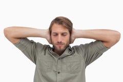 Bemannen Sie das Blockieren seiner Ohren und das Schließen seiner Augen Stockfoto