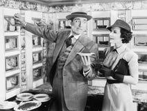 Bemannen Sie das Dienen eines Tellers zu einer Frau in einem Automaten (alle dargestellten Personen sind nicht längeres lebendes  Stockfoto