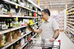 Bemannen Sie das Einkaufen und das Betrachten des Lebensmittels im Supermarkt Lizenzfreies Stockbild