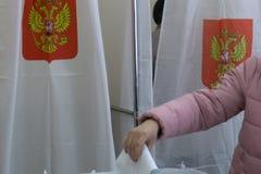 Bemannen Sie das Einsetzen des Stimmzettels in einen Kasten während der Wahlen in Russland Lizenzfreie Stockfotografie