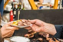 Bemannen Sie das Empfangen der köstlichen argentinischen Steakfingermahlzeit am offenen Lebensmittelmarkt in Ljubljana, Slowenien Stockfoto