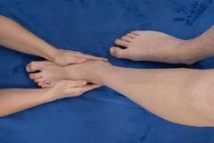Bemannen Sie das Empfangen einer Fußmassage durch einen weiblichen Masseur Stockbilder
