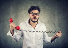 Bemannen Sie das Empfangen von schockierenden Nachrichten an einem Telefon, das besorgt sich fühlt stockfotos