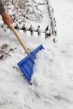 Bemannen Sie das Entfernen des Schnees vom Bürgersteig nach Schneesturm Stockfotos
