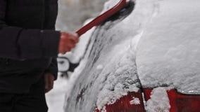 Bemannen Sie das Entfernen des Schnees von einem Auto nach großem Schneesturm stock footage