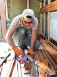 Bemannen Sie das Errichten eines Hauses und des workimg mit Holz lizenzfreie stockbilder