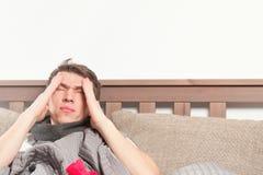 Bemannen Sie das fühlende schlechte Lügen im Bett und das Husten lizenzfreie stockbilder