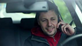 Bemannen Sie das Fahren des Autos, welches das Telefon auswählt und zu den Passanten wellenartig bewegt stock video footage